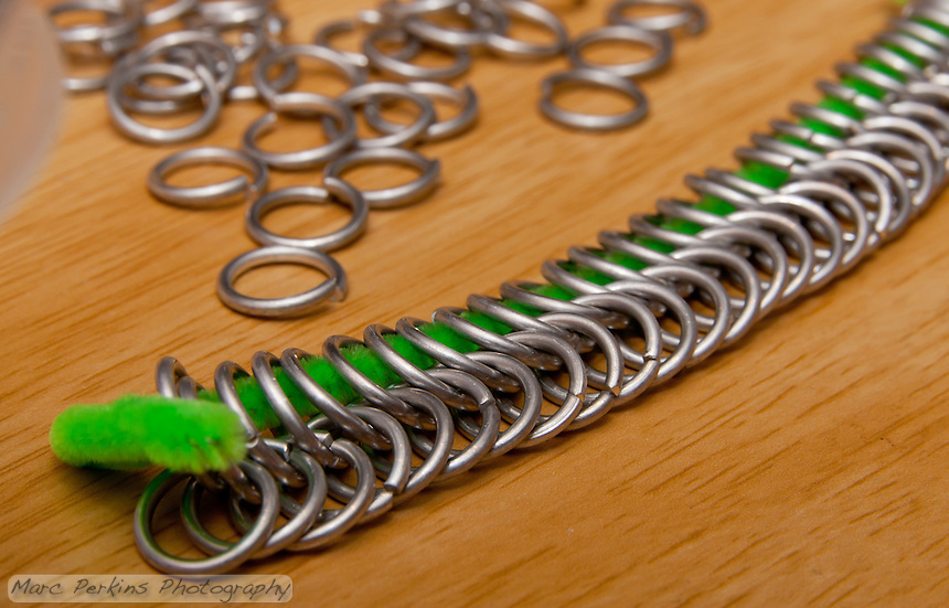 Two rows of aluminum chain mail rings joined together, with a scattering of rings in the background.