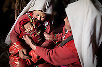 Kelt Baig's 2 wives. His first wife's (right) kids always died and so Kelt Baig had a second wife who had a son who so far survived the dificult conditions in the Pamir. Both wives seemed very happy to have a baby son in the household. Sary Tash campement...Trekking with yak caravan through the Little Pamir where the Afghan Kyrgyz community live all year, on the borders of China, Tajikistan and Pakistan.