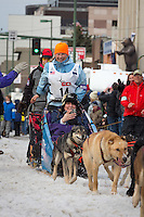 Gwenn Bogart and team leave the ceremonial start line with an Iditarider at 4th Avenue and D street in downtown Anchorage, Alaska during the 2015 Iditarod race. Photo by Jim Kohl/IditarodPhotos.com