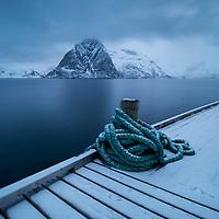 Wooden quay in winter on shore of Reinefjord, Lofoten Islands, Norway