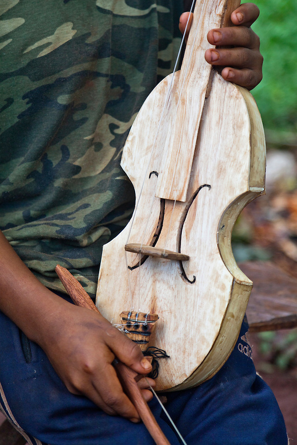 Angel Morinigo, an Mbya Guarani craftsman and musician from Andresito village near San Ignacio, Misiones, Argentina, hand-building a Guarani 3-string violin (rabe).  His son demonstrates the finished violin.