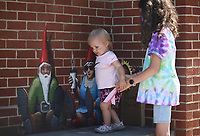 Addison Cash, 16 months, is helped by her sister MaKayden (cq), 12, as she walks on a bench past two gnomes painted on the wall by artist Jason Jones on the square in Fayetteville. The girls were with family taking a discovery field trip to get some exercise outside of their home. Check out nwaonline.com/200626Daily/ and nwadg.com/photos for a photo gallery.<br /> (NWA Democrat-Gazette/David Gottschalk)