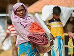 A Rohingya woman carries a tarp, blankets and other items that she received from Christian Aid in the Jamtoli Refugee Camp near Cox's Bazar, Bangladesh. Christian Aid is a member of the ACT Alliance.<br /> <br /> More than 600,000 Rohingya have fled government-sanctioned violence in Myanmar for safety in Bangladesh.