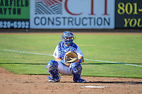 Hunter Redman (5) of the Ogden Raptors warms up the starting pitcher  in the bullpen before the game against the Idaho Falls Chukars in Pioneer League action at Lindquist Field on June 23, 2015 in Ogden, Utah. Idaho Falls beat the Raptors 9-6. (Stephen Smith/Four Seam Images)