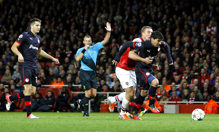 The referee objects to Arsenal's Lukas Podolski 's tackle on Olympiakos' Pablo Contreras ..Football - UEFA Champions League Group B - Arsenal v Olympiakos FC - Wednesday 3rd October 2012 - Emirates Stadium - London..