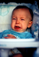 A six month old baby boy cries while sitting in his highchair.