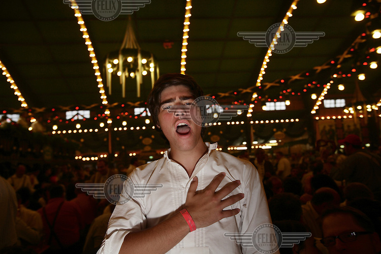A happy youngster singing along to a Bavarian band. The Munich Oktoberfest takes place each year over 16 days, and is known as the Largest Volksfest (People's Fair) in the World, attracting upwards of 6 million people, who in turn consume close to 7 million litres of beer...