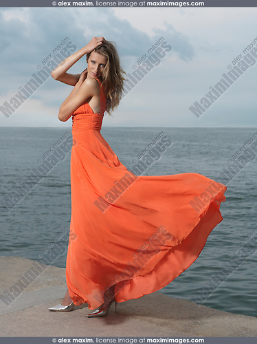 Beautiful woman in bright dress flying in the wind on a sea shore