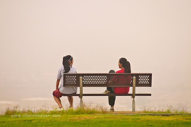 Two young girls taking a break during their morning walk at Panorama Park, Bakersfield, California.