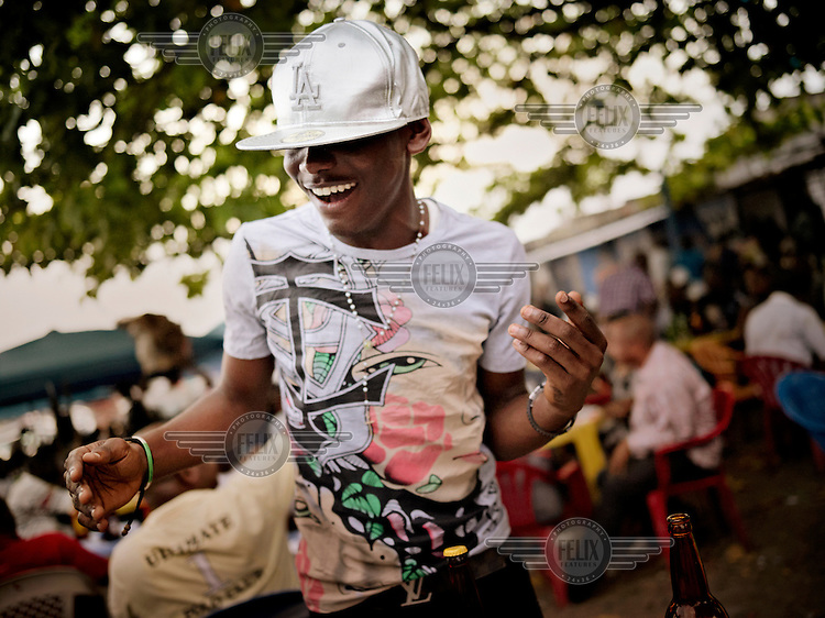 17 year old Eric dances at an outdoor bar in Kinshasa. The middle classes almost don't exist in D.R. Congo; the more wealthy youngsters have relatives living in Europe.