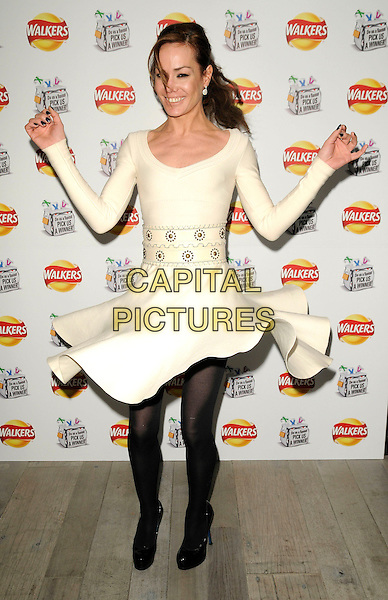 TARA PALMER TOMKINSON .At the Walkers' Crisps Do Us A Flavour Launch Party, CenterPoint , New Oxford Street, London, England, .8th January 2009..full length cream long sleeved dress black tights hands twirl twirling patent shoes platforms  .CAP/CAN.©Can Nguyen/Capital Pictures