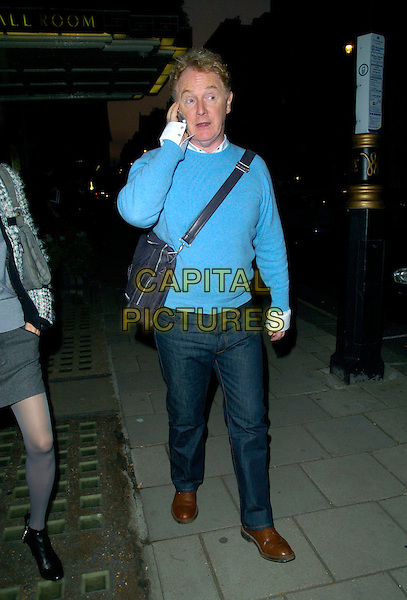 MALCOM McLAREN .Spotted outside Claridge's Hotel, London, England, October 14th 2007..full length blue jumper talking on mobile phone jeans bag white shirt brown shoes                                                         .CAP/CAN.©Can Nguyen/Capital Pictures