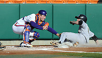 Matthew Ramsay (19) of the Wofford Terriers is tagged out by Clemson Tigers catcher Garrett Boulward (30) trying to score on a hit by Josh Hyman in the first inning of a game on Wednesday, March 6, 2013, at Doug Kingsmore Stadium in Clemson, South Carolina. Clemson won, 9-2. (Tom Priddy/Four Seam Images)