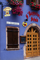 France, Alsace, Ribeauville, Haut-Rhin, Europe, wine region, Flowers decorated the colorful purple entrance to a Brasserie (restaurant) in the village of Ribeauville in the wine region of Alsace.