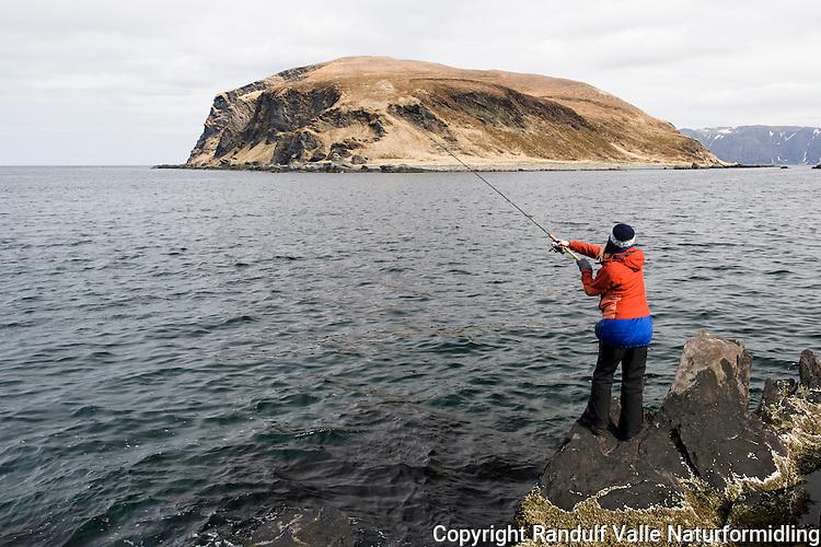 Jente fisker med sluk i sjøen ved Kamøyvær på Magerøya. ----- Girl lure fishing at Kamøyvær.