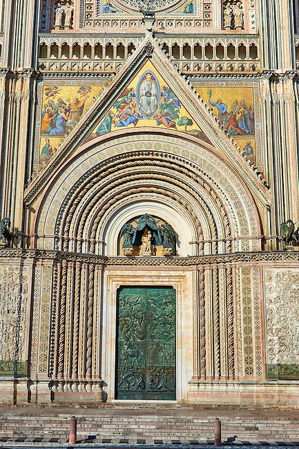 Close up of the main door with mosaics depicting the the Virgin Mary created between 1350 and 1390 after designs by artist Cesare Nebbia on the14th century Tuscan Gothic style facade of the Cathedral of Orvieto, designed by Maitani, Umbria, Italy