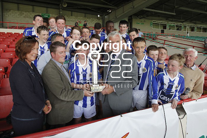 XX SPORT 07/07/2013 Oliver Mann, Chairman of Limerick County Board presents Ross McCormack, Captain of Ballyboden St Enda's with the Feile Na nGael Division 1 Trophy after his team beat Douglas in the final at the Gaelic Grounds, Limerick. Picture: Don Moloney / Press 22