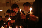 Brothers of the Delta Sigma Phi fraternity bow their heads at the end of the Candlelight Vigil for Alex Ehr in the Newman Center in Lexington, Ky., on 2/23/12. Photo by Brandon Goodwin | Staff
