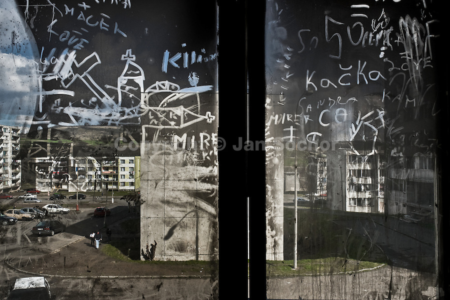 The Gipsy ghetto of Chanov seen through a dirty window, covered by writings, in a devastated empty apartment block on outskirts of Most, Czech Republic, 26 March 2008.