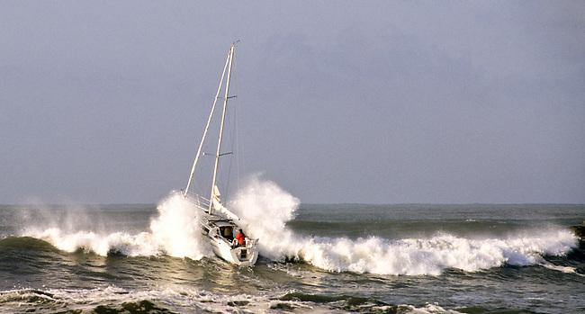 Sailboat crashing through surf leaving Oceanside harbor.