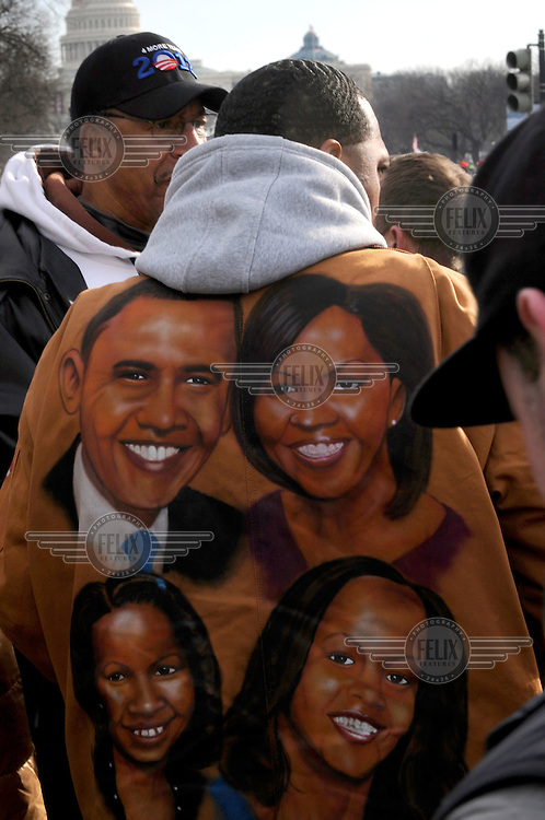 Hundreds of thousands of people pack The Mall in front of the White House in Washington D.C to cheer on President Barack Obama for his second inauguration. A man wears a jacket showing a picture of the First family..
