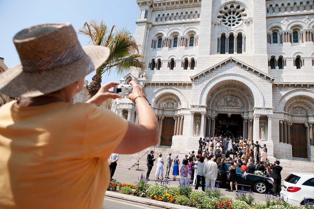 A passer-by photographs a wedding party on the steps of Monaco Cathedral, Monaco, 6 July 2013