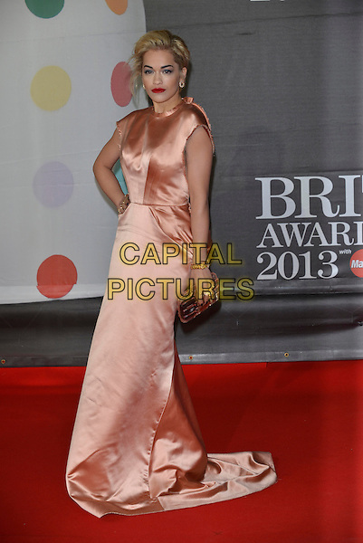 Rita Ora.The Brit Awards 2013 arrivals at the O2, Greenwich, London, England 20th February 2013.The Brits  full length peach dress silk satin halterneck ruched long maxi hand on hip gold clutch bag train.CAP/PL.©Phil Loftus/Capital Pictures.