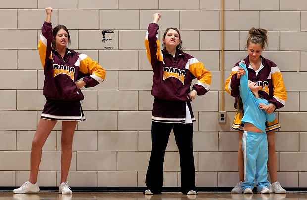 Four-year-old Kalie Gillespie, right, of south Des Moines learns some cheerleading moves from Lincoln cheerleader Jessica Belieu during the sophomore boys basketball game at Roosevelt Friday, February 17, 2006.  Cheering with them are Megan Lyons (left) and Paige Metzger.
