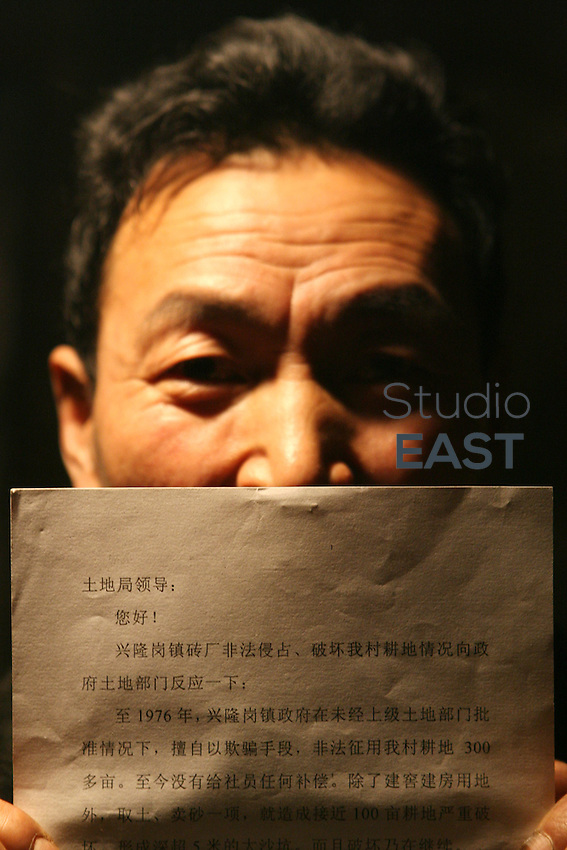 Farmer Wu Fengjiang, 55, shows a letter he wrote to local government officials complaining about a brick factory that is encroaching on farmland in his neighboring home village of Yongan, on February 27, 2006. Photo by Lucas Schifres/Pictobank