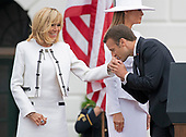 President Emmanuel Macron of France kisses the hand of his wife, Brigitte Macron, at the conclusion of an arrival ceremony on the South Lawn of the White House in Washington, DC on Tuesday, April 24, 2018. First lady Melania Trump is pictured behind them.<br /> Credit: Ron Sachs / CNP