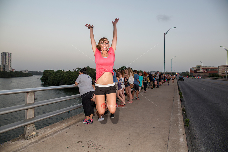 Cheerful attractive Austin woman jumps for joy on the Congress Ave. Bat Bridge in downtown Austin, Texas.