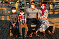 """I was struck by the sweetness of this family sitting at Riverside Park, lined up tightly ensconced in their protective facemasks, enjoying the gorgeous setting of the sun. On a nice day in New York City, when more than a few people finally emerge from their elongated isolation, it's remarkable to witness a whole city wearing facemasks. I'm still in the beginning stages of finding the phenomena strange. I imagine within time, as the city begins to slowly open up from its long deep sleep, the look will seem more commonplace. We hope so anyway. The funny thing about New Yorkers, I felt like we were always wearing masks before anyway, we just couldn't see them. Now the masks almost seem like a common bond, a statement, I care about you and your loved ones. We are all in this together. <br /> <br /> It turns out the Khan's are doctors. She works at the children's hospital in Washington, DC. He's a resident doctor at Yale. So even though they were married three months ago Tayyba and Sameer are forced to live apart right now. They're visiting their extended Pakistani family and had brought their two gorgeous nephews to the park. She told me their story just as the sun finished setting and then got up to leave. """"And now if you'll please excuse us, we need to go break our fast."""" <br /> <br /> For those of us who missed family time during Easter and Passover, Ramadan is considered one of the holiest months of the year for Muslims. In accordance with the Qur'an, during this time they fast from food and drink during the sunlit hours as a means of learning self-control, gratitude, and compassion for those less fortunate. Thank you so much to the Khan's for your service and sacrifices. I'm wishing you and Muslim's everywhere a blessed Ramadan!"""
