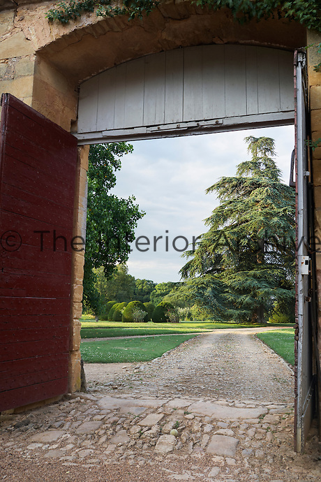 View through open double doors to the driveway of the Chateau de la Bourlie, Dordogne