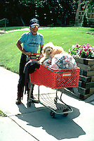 Homeless man age 45 pushing cart of aluminum cans with dog.  Minneapolis Minnesota USA