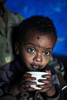 BONGA, ETHIOPIA:  A child drinks coffee sitting in his mother's lap on December 3, 2012 in Duberasha outside Bonga, Ethiopia. The Kaffa region is known for its coffee production, wild coffee grown in high altitudes. This region is the original home of the coffee plant, coffee Arabica which grows in the forest of the highlands. The red berries are the main source of income in the area. Children and cattle also drink coffee. (Photo by: Per-Anders Pettersson)