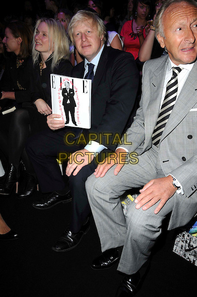 BORIS JOHNSON.The Caroline Charles Spring/Summer 2010 catwalk show during London Fashion Week at the BFC Tent, Somerset House, London, England..September 18th, 2009.LFW full length blue black suit mayor sitting elle magazine.CAP/CAS.©Bob Cass/Capital Pictures.