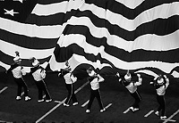 Husky Band members wrangle the American flag as it unfurls during pregame.