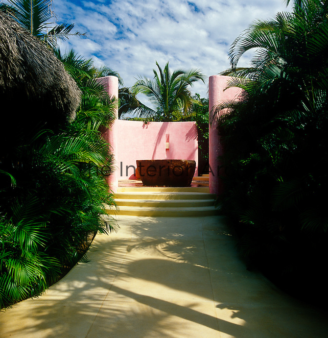 A smooth cement path leads up to a large stone fountain  surrounded by pink walls