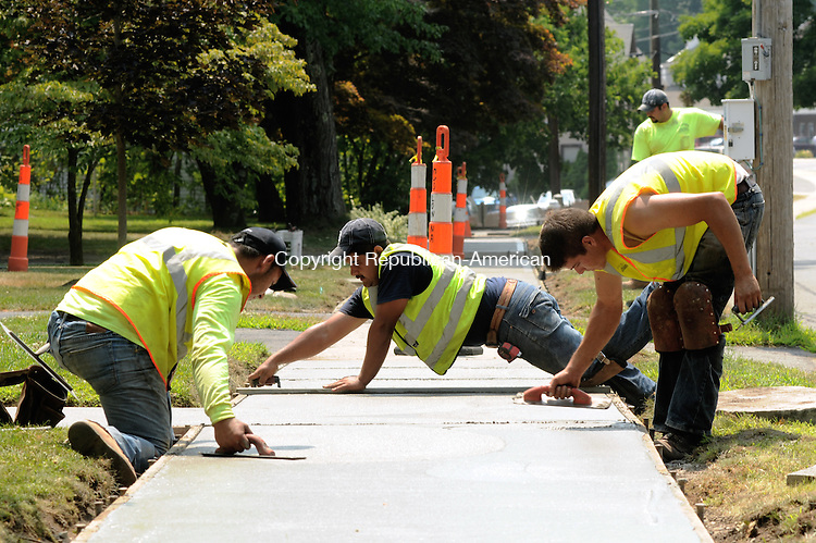 THOMASTON, CT 07  JULY, 2010-07070JS03-Workers from Colonna Concrete and Asphalt Paving of West Haven, float freshly poured concrete as they replace the sidewalks and curb cuts on Elm Street in Thomaston on Tuesday. The entire length of sidewalk on both sides of the road are in the process of being replaced. In addition to Elm Street, other streets that are part of a sidewalk Improvement Project are Hillside Avenue, Gilbert Street, Union Street and Oak Street.Jim Shannon Republican-American