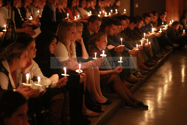 Hundreds of students, faculty and staff sit with lit candles at the candlelight vigil for Alex Ehr in the Newman Center in Lexington, Ky., on 2/23/12. Photo by Brandon Goodwin | Staff