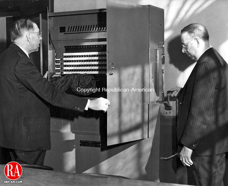 1950 - The day after the election Peter H. Dunais, left, and Peter B. Lynch, right, official custodian and assistant custodian of the voting machines, visited each of the 36 voting precincts and prepared the machines for their return trips to the storage room.  This meant cranking down the upper part of each machine, closing the metal doors, and covering them with either canvas or metal covers to keep them from being damaged in transit.  Republican-American Archives