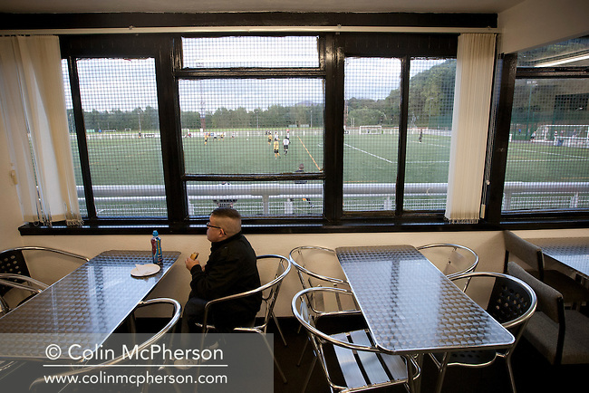 A fan sitting eating in the club's new cafe during Gala Fairydean Rovers' first home match in the Scottish Lowland Football League against Edinburgh City at Netherdale in Galashiels. Gala were formed in 2013 by an a re-amalgamation of Gala Fairydean and Gala Rovers, the two clubs having separated in 1908 and their ground in the Scottish Borders had one of only two stands designated as listed football stands in Scotland. The match ended in a 3-3 draw watched by 378 spectators.