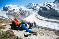 A man lays on a rock relaxing in the sun with views of the Monte Rosa, Switzerland.