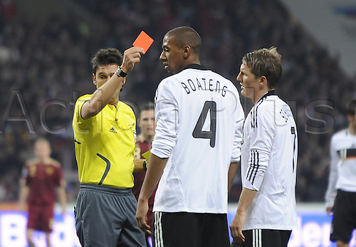 Swiss referee Massimo Busacca (L) shows the yellow-red card to Germany's Jerome Boateng (C) during the World Cup 2010, Group 4 qualifier Russia vs Germany at Luzhniki Stadium in Moscow, Russia, 10 October 2009. Germany won 1-0.