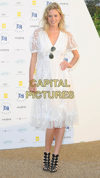 Natasha Gilbert.Attends Chucs Dive & Mountain Shop Swim Party in aid of charity: water at The Serpentine, London, England..July 4th, 2011.full length white sheer dress clutch bag black sandals sunglasses shades aviators hand on hip.CAP/BEL.©Tom Belcher/Capital Pictures.