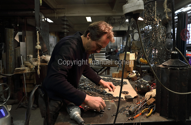 Nicolas Desbons, metalworker and artist, assembling steel pieces for a sculpture made from cross-sections of steel tubes manipulated into organic profiles and soldered together, in his Soleil Rouge workshop, photographed in 2017, in Montreuil, a suburb of Paris, France. Desbons works mainly in steel but often in conjunction with other materials such as fibreglass, glass and clay, using both cold metal and forge techniques. He produces both figurative and abstract sculptures as well as furniture and lighting. Picture by Manuel Cohen