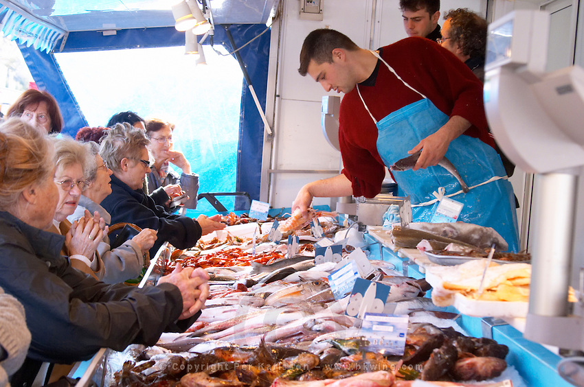 Street market merchant's stall with many different type of fish shopping ladies fighting to get the best pieces Sanary Var Cote d'Azur France