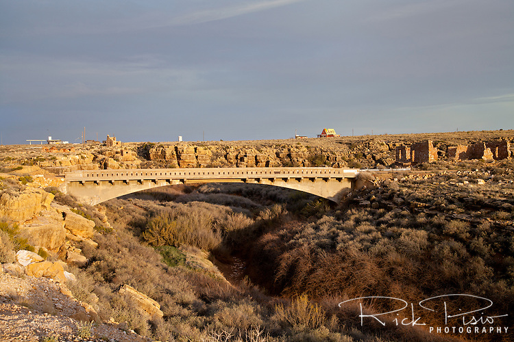 """Route 66 Bridge over Diablo Canyon at Two Guns, Arizona. Two Guns is located in Arizona, east of Flagstaff, on what was formerly Route 66. Two Guns was originally called """"Canyon Lodge"""" when the National Trail Highway moved westward. Later, the National Trail was re-named Route 66, the site's name was changed to Two Guns, because the proprietor of the facilities located there was one Henry E. Miller, who called himself """"Two Gun Miller.""""  During the heyday of Route 66, Two Guns became one of the numerous tourist traps along the way, with a gas station, overnighting accommodations, a food emporium, as well as a zoo. Two Guns went into decline with the building of the Interstate."""