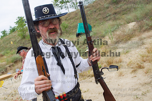 Competitor carries his weapons for inspection during the Cowboy Action Shooting European Championship in Dabas, Hungary on August 11, 2012. ATTILA VOLGYI