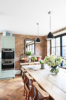 A large wooden kitchen table with oak chairs salvaged from a church . It's large enough to seat 14 people and, together with the varied rust tones of the bare-brick walls, lends the space an earthy, warm feel